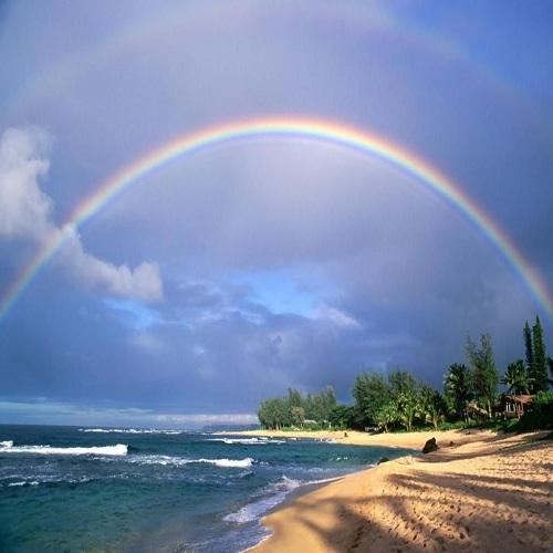 Double rainbow and evening light on beach. Kauai Island. Hawaii. USA